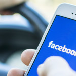 man-driving-while-holding-mobile-facebook-app