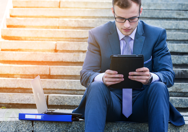 young businessman sitting on stone steps reading tablet