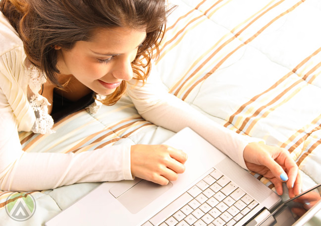 female-customer-on-bed-looking-on-her-laptop