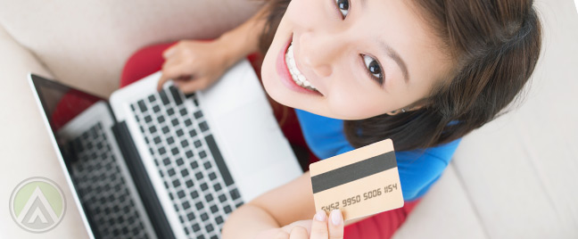 female-customer-holding-laptop-and-credit-card