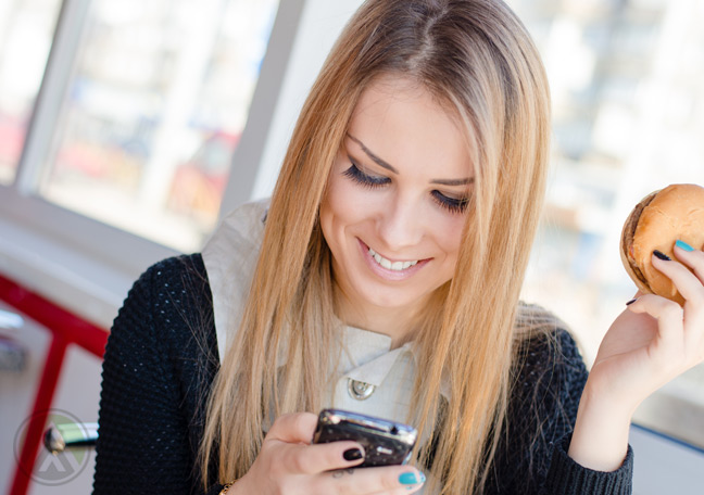 blond-females-using-sms-smartphone-while-having-a-burger
