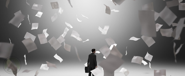 businessman-in-middle-of-falling-piles-of-paper