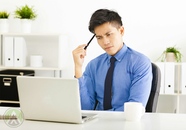 male-asian-businessman-thinking-in-front-of-laptop