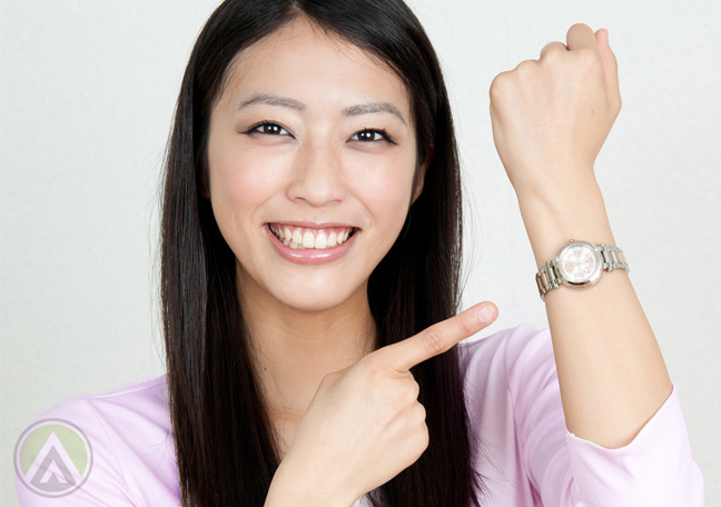 smiling-Asian-woman-pointing-to-watch