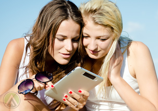 blonde-brunette-women-reading-from-a-tablet