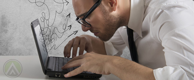 businessman-in-glasses-working-on-laptop-netbook-computer-looking-closely