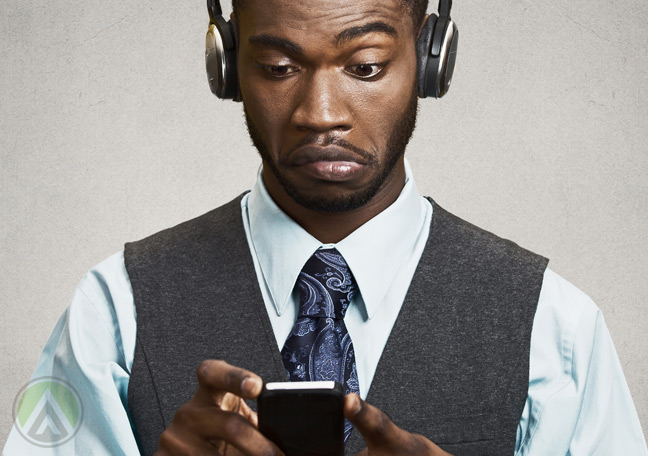 confused-African-American-businessman-in-black-wearing-headphones-looking-at-smartphone