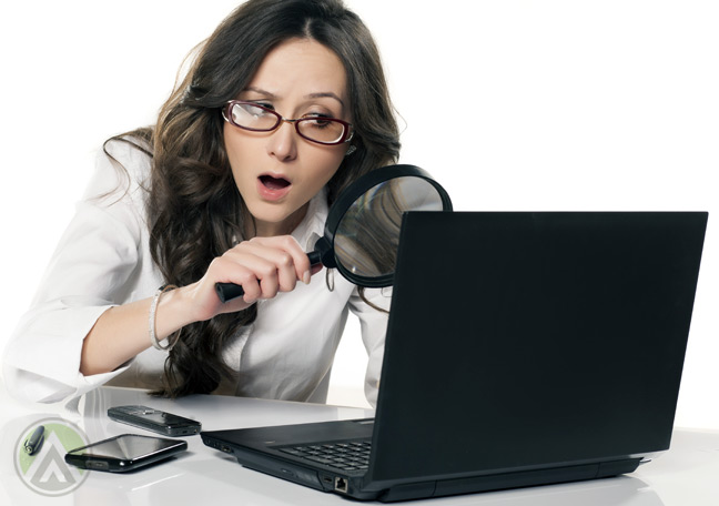 confused-female-employee-searching-on-laptop-with-magnifying-lens