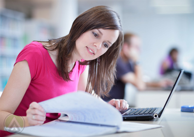 female-employee-in-pink-reading-from-paper-and-on-laptop