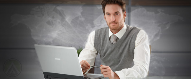 male-employee-using-business-laptop-with-world-map-backdrop
