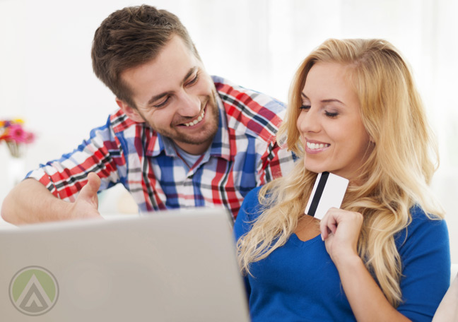 smiling-couple-on-ecommerce-site-on-laptop