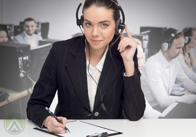 female-quality-assurance-agent-listening-to-customer-service-call-with-call-center-agents-in-the-back