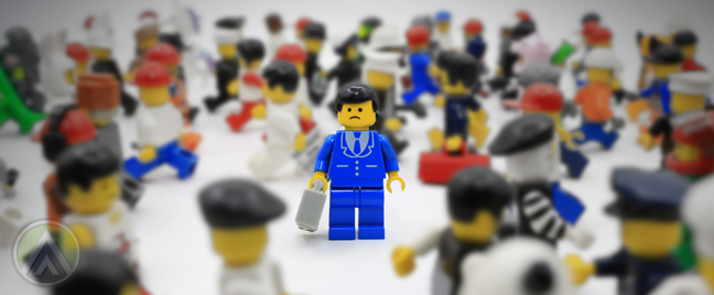 Lego-minifigures-busy-blurred-sad-ignored-figure-in-blue-business-suit-in-the-middle