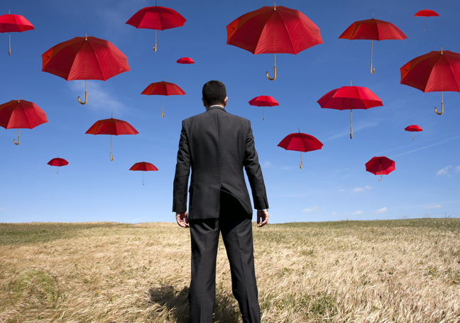businessman-in-suite-standing-in-middle-of-the-field-looking-up-at-blue-sky-with-floating-red-umbrellas