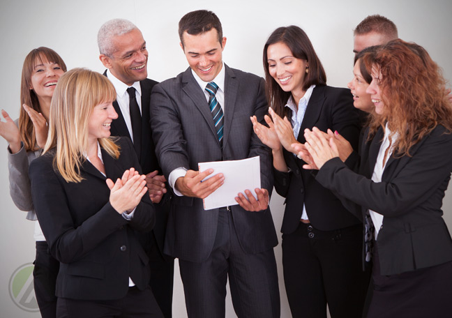 diverse-business-team-applauding-member-reading-paper-document