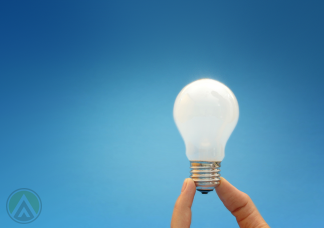 fingers-holding-a-lit-lightbulb-amid-blue-background