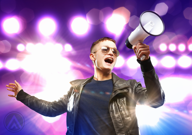 man-in-leather-jacket-and-glasses-shouting-on-megaphone-with-bright-purple-backdrop