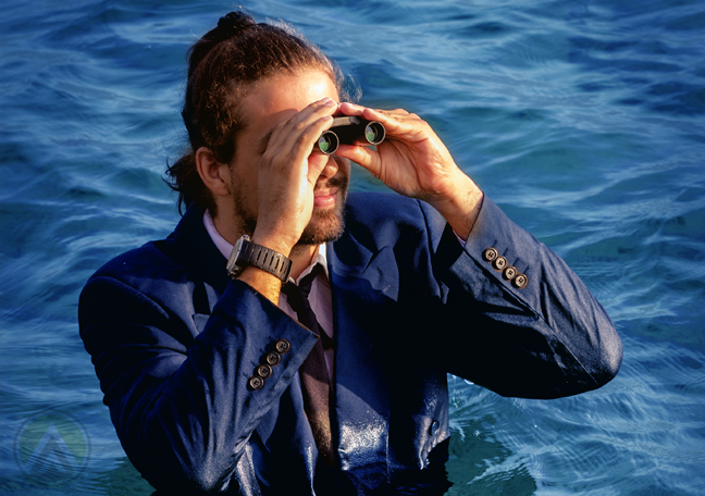 bearded-long-haired-businessman-in-the-ocean-lookign-through-binoculars