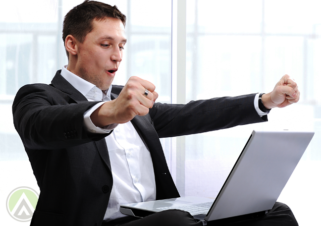 businessman-with-laptop-fist-in-air
