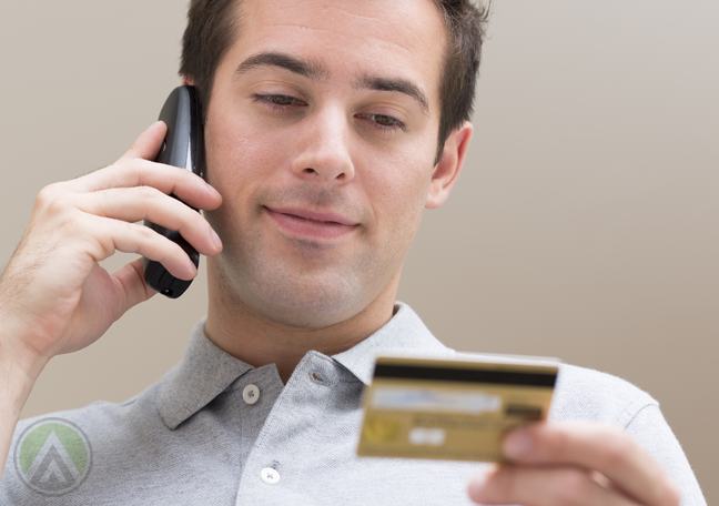 man-in-phonecall-while-looking-at-credit-card