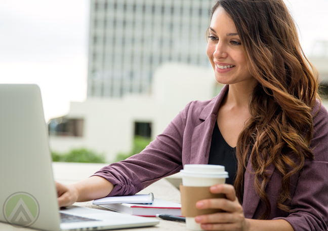 smiling-brunetter-woman-holding-coffee-cup-using-laptop