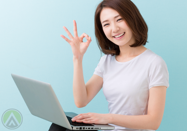 smiling-female-Asian-using-laptop-excellent-hand-sign