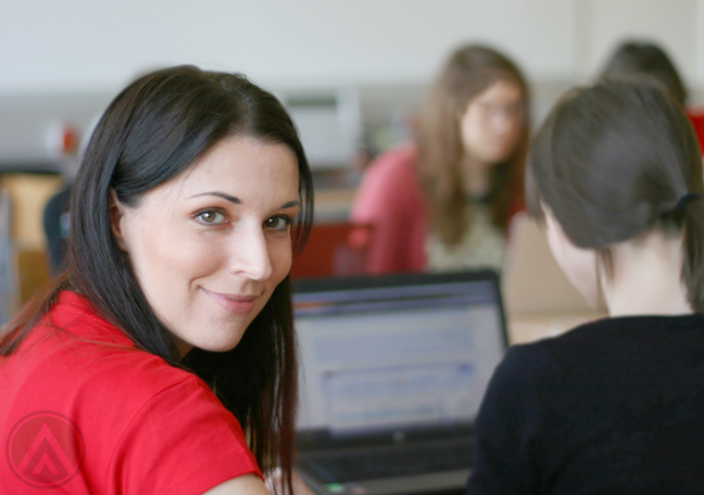 smiling-woman-in-red-behind-woman-busy-working-computer