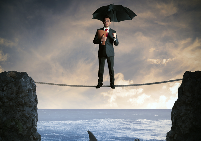businessman-using-umbrella-standing-on-tight-rope-above-ocean-with-sharks