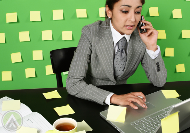 female-business-executive-on-phone-call-using-laptop
