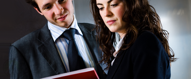 male-female-business-executives-looking-dubious-at-red-folder
