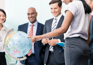smiling-diverse-business-team-looking-pointing-to-globe