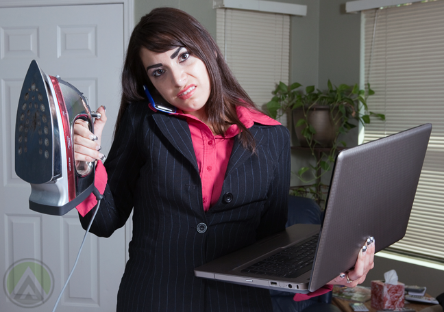 annoyed-young-woman-milennial-in-business-garb-holding-flat-iron-laptop