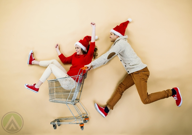 couple-in-santa-hat-rushing-to-store-on-shopping-cart