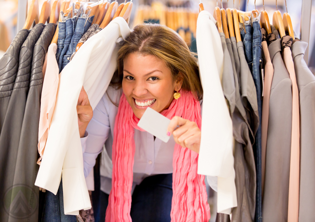 delighted-woman-smiling-brightly-holding-credit-card-in-the-middle-of-clothes