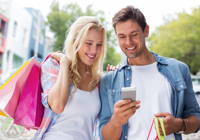 female-male-couple-with-shopping-bags-smiling-over-smartphone