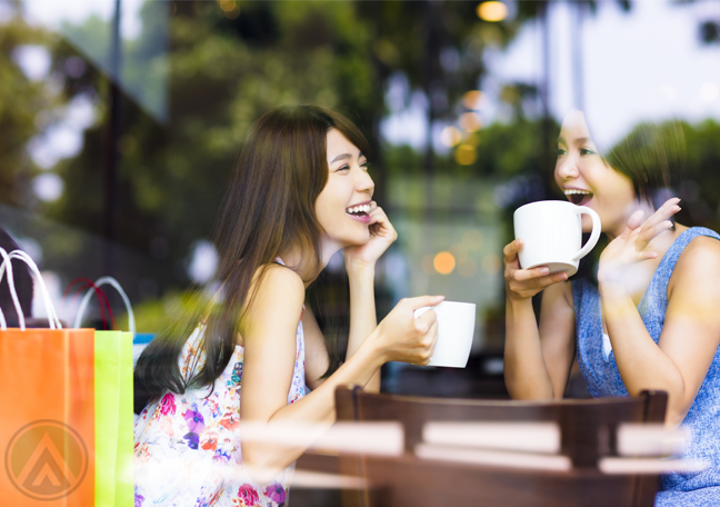 women-at-cafe-shop-laughing-over-coffe-with-shopping-bags