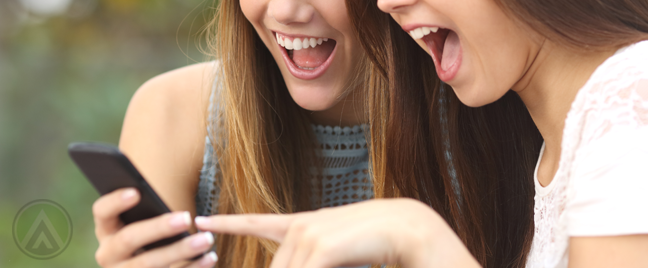 happy-excited-women-looking-at-smartphone