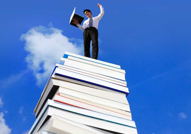 businessman-using-lalptop-on-stack-of-books