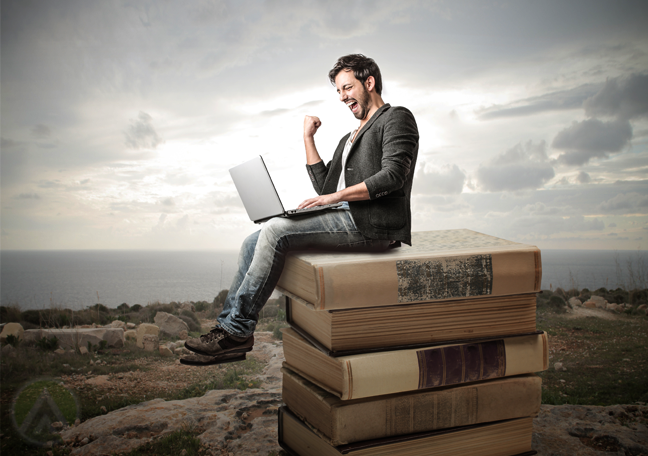 excited-man-using-laptop-sitting-on-stack-of-giant-book-in-desert