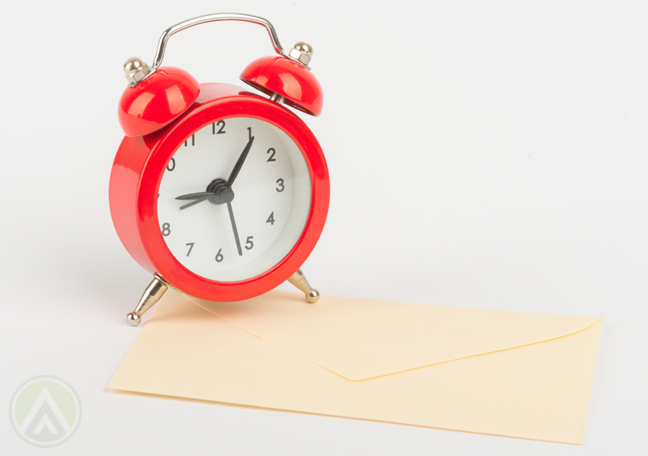 red-alarm-clock-on-yellowing-letter-envelope