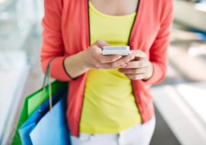 woman-with-shopping-bags-looking-at-smartphone