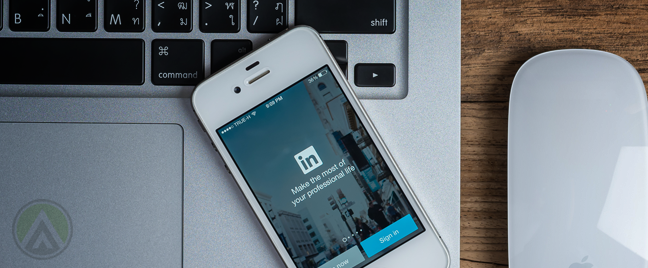 LinkedIn-mobile-app-on-iPhone-on-open-Macbook-keyboard-next-to-might-mouse