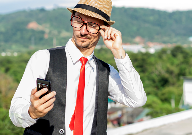 young-man-with-glasses-looking-at-smartphone-outdoors