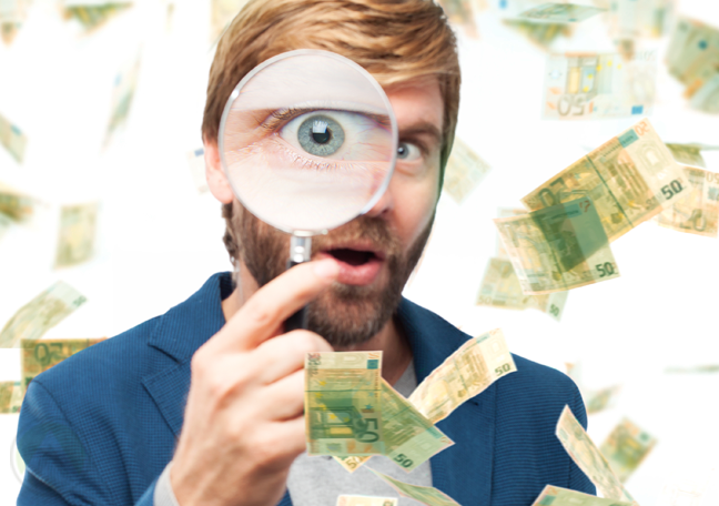 bearded-man-using-magnifying-lens-with-flying-money
