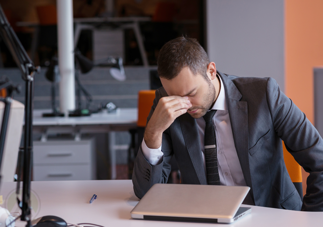 businessman-with-headache-frustrated-in-front-of-closed-laptop