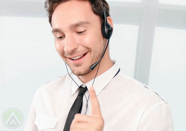 male-call-center-agent-looking-down-speaking-to-customer-on-call
