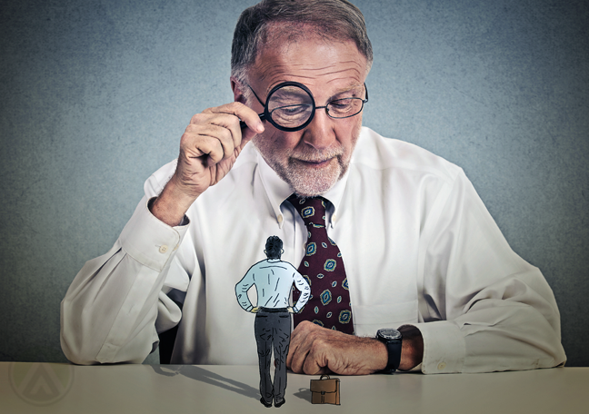 midldle-aged-businessman-looking-at-smaller-employee-through-magnifying-lens
