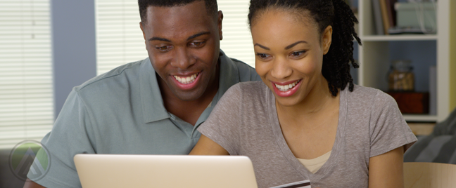 smiling-couple-looking-at-laptop-computer