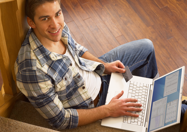 smiling-young-man-using-laptop-on-the-stairs-landing