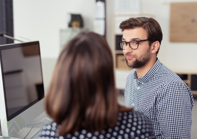bearded-employee-in-glasses-in-serious-conversation-with-female-boss